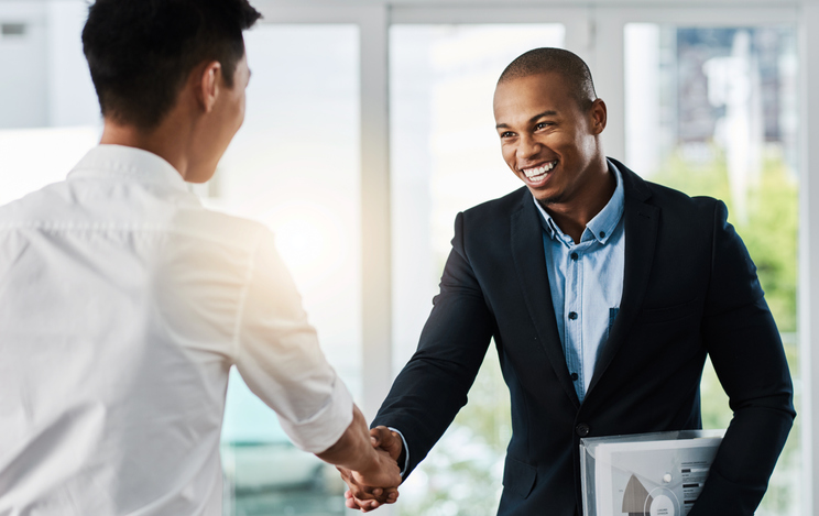 Two young businessmen shaking hands after one of them landed a new job.